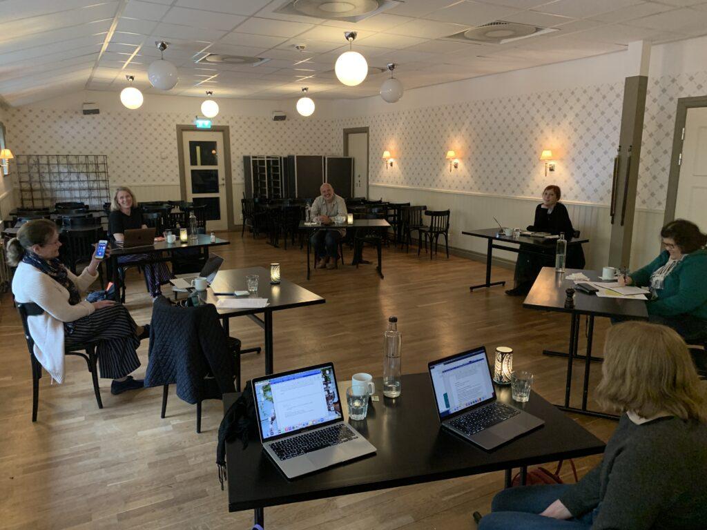 Projektgruppen sitter spridda i ett rum vid sina bord. I mitten sitter Helena och håller upp en telefon.